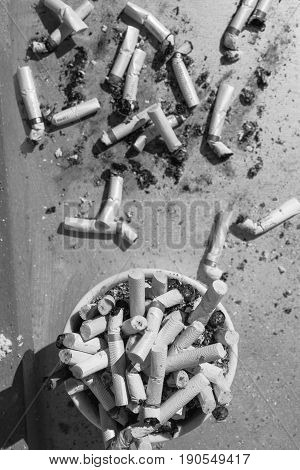 Ashtray full of cigarette stubs and some of them outside the tray