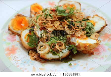 Fried boiled eggs with sweet and sour sauce topped with fried garlic red onion and cilantro ( selective focus on center of eggs)