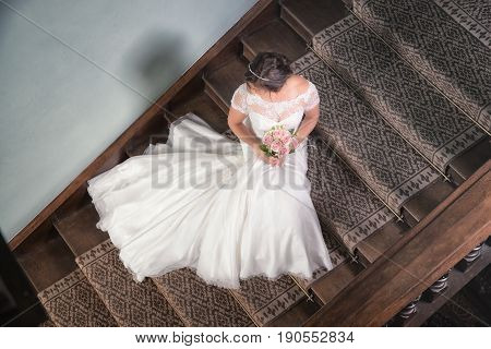 Looking Down Onto A Bride Sat On The Stairs With Her Wedding Dress Fanned Out