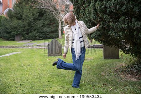 Lady Checks Her Shoe In Graveyard For Dog Poo
