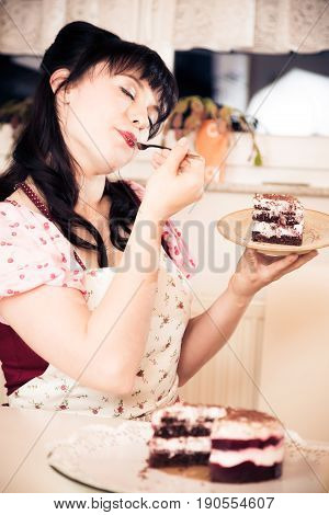 girl in vintage style dress enjoying a piece of cake