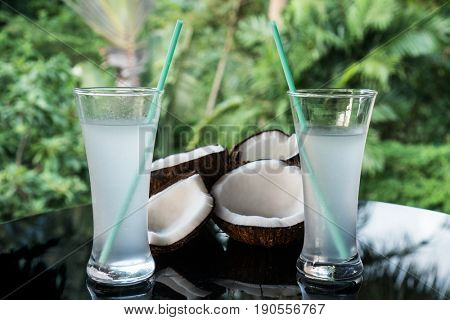 Closeup of coconuts and coconut water on the black glass table isolated over blurred palm trees background
