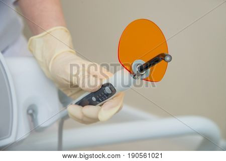 Hand in medical glove holding Dental UV curing light. Ultraviolet polymerization Lamp with orange blocking glass.