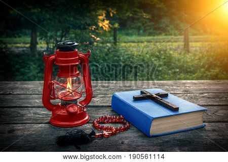 Wooden christian cross on bible burning kerosene lamp and prayer beads on the old table. Church utensils. Salvation of soul and expiation of sins. Religious confession. In god we trust. Christianity.