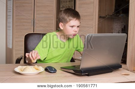 Teen boy eating potatoes chips and surfing on internet or playing video games on laptop. Kid in headphones eating chips while using pc in his room.