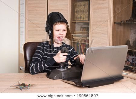Happy boy playing online pc game. Emotional kid play and win video games.