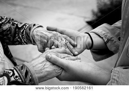 Young hands supporting old hands-helping elderly people concept-black and white image with selective focus.
