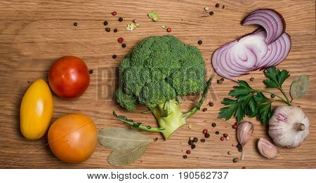 Fresh broccoli cut into halves with tomatoes garlic and spices prepared for cooking close up. Vegan food vegetarian and healthily cooking concept. Bunch of fresh green broccoli with ingredients on wooden background. Top view selective focus.