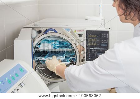 Denatal assistant using Sterilization systems. Preparation instruments for cleaning.