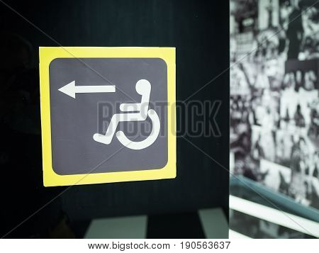 sign for disabled on a black background. Direction indicator for wheelchair users