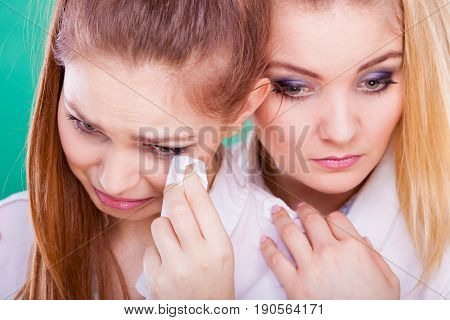 Young woman is sad crying and being consoled by friend. Girl comforting her sister. Mental problems depression and fatigue.
