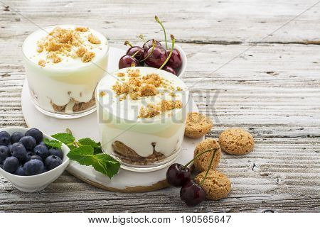 Healthy summer dessert of berry yogurt almond cookies portioned in glass cups on a light wooden background with ripe blueberries and juicy cherries. Selective focus. the concept of fitness nutrition.