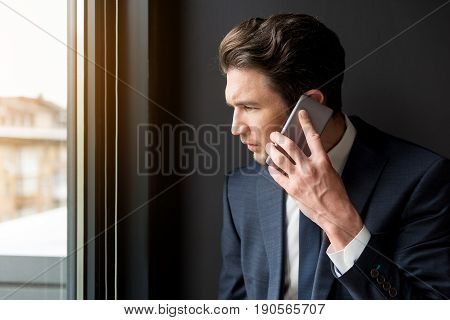 Bad news. Profile of depressed young man is talking on smartphone while looking through window hopelessly. Copy space in the left side