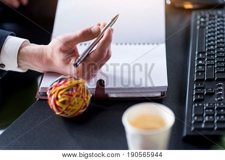Personal diary. Man in suit is making notes on his notepad while sitting at desk with keyboard and coffee. Close up of hand with pen and multicolored ball. Selective focus