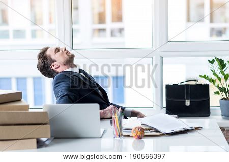 Feeling empty. Young overworked and overwhelmed businessman is expressing fatigue while sitting at his workplace