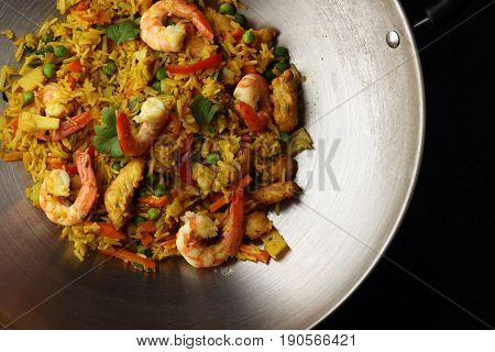 Udon Stir-fry Rice With Shrimp And Vegetables In Wok Pan On Black Burned Stone Background