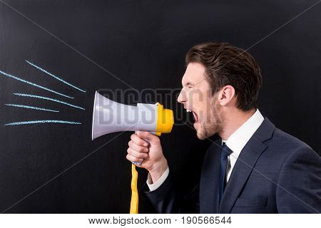 Aggressive management concept. Angry young man is screaming through megaphone while standing against dark background