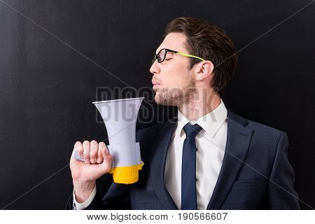 Funny concept. Attractive young businessman with stubble is blowing on megafone pretending to shoot with it. dark background