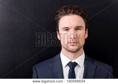Confident and successful. portrait of young pleasant businessman with stubble is looking at camera seriously. dark background