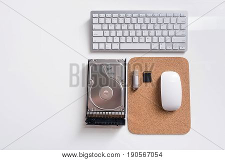 Close-up top view of white table with keyboard and other computer tools. Copy space in the left side