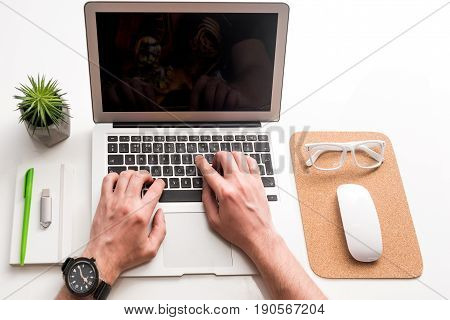 Rapid changes of life. Close up top view of laptop and other stuff are on white table while hands of man are typing on keyboard
