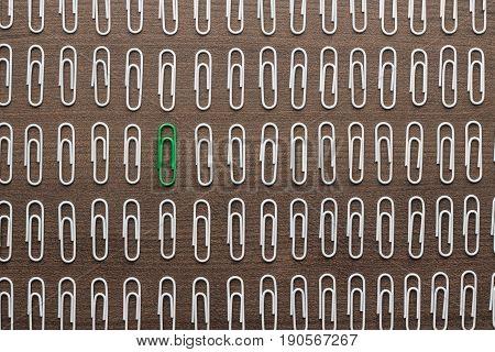 bright green paper clip unique idea concept. stand out of the crowd uniqueness concept. uniqueness concept on brown table. top view of uniqueness concept out of paperclips. uniqueness concept on wooden background.