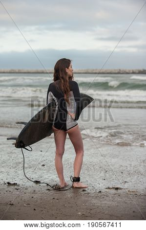 Sexy California surfer girl in portrait view holding surf board under arm while checking the waves.