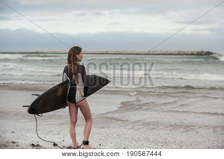 Sexy California surfer girl in landscape view holding surf board under arm while checking the waves.
