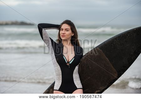 Sexy California surfer girl holding board and hair back in landscape orientation.