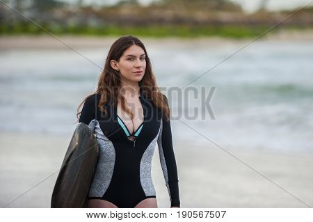 Sexy California surfer girl holding surf board while walking along shore in close view.