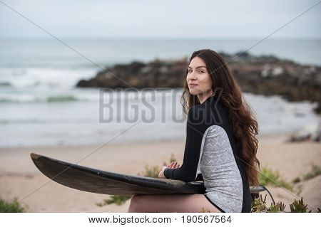 Sexy California surfer girl holding surf board on lap smiling to left.