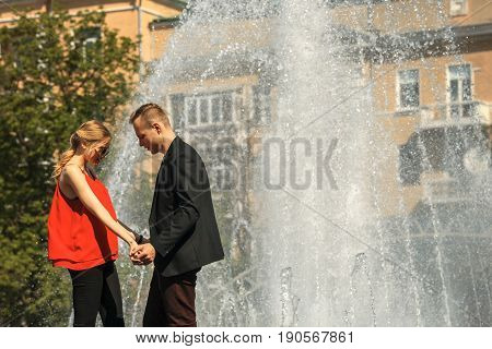 Couple In Love Next To The Fountain On A Sunny Day.