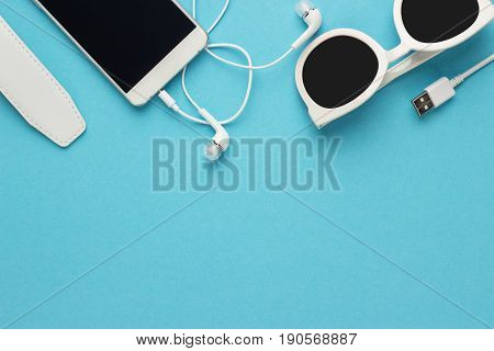 studio shot of white sunglasses smart phone and earbuds summer concept. on blue background