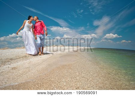 Bride and groom walking in sunshine on a beautiful tropical beach