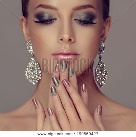 Beautiful model girl with pink and silver  metallic manicure on nails . Fashion makeup smokey eyes and cosmetics . Big silver diamond Shine  earrings jewelry