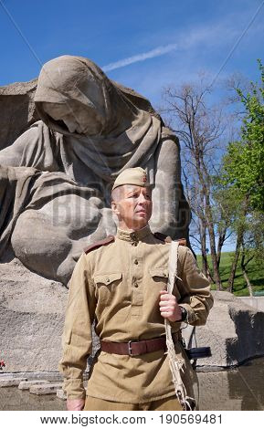 Fighter of Red Army in the form of times of World War II with the machine gun at a historical monument (fragment)