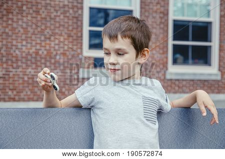 boy sitting by the school with a fidget spinner. child is playing with a spinner