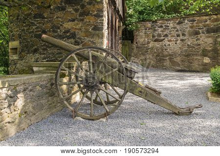 The photo shows an old, historic cannon. It is located on wooden wheels, stands in the area of Czocha castle located in the village of Leśna in south-western Poland. In the background you can see fortifications in the form of a defensive wall. It is sunny