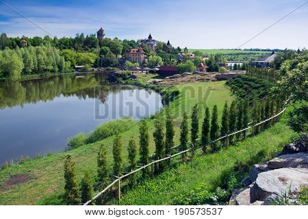 A lake in the middle of a green garden with forest and residence in a Mezhyhirya Residence in Ukraine