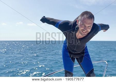Scuba diver on boat putting on his wetsuit.