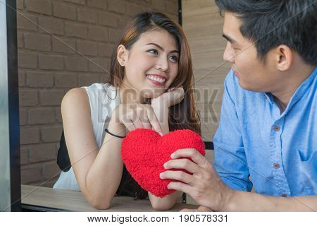 Young couples looking at each other. Beautiful girl put a hand on the red heart in hands of the young man.