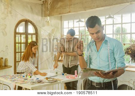 Young asian male designer standing with designer team working in the studio.