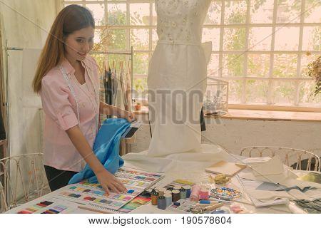 asian female dressmaker or designer choosing a fabric color in her workshop.