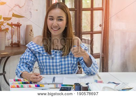 asian female dressmaker or designer thumbs up and smiling happily with sewing accessories.
