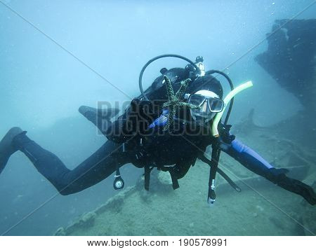 Scuba diver exploring underwater shipwreck. Scuba diving blue water.