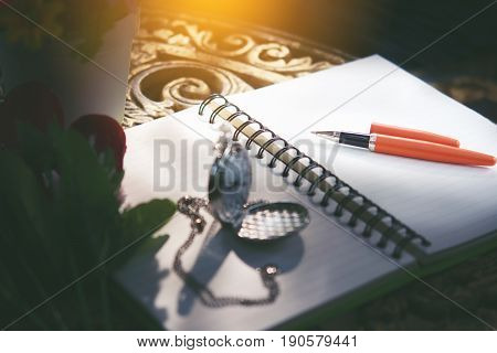Pen and pocket watch on a white notebook on a table