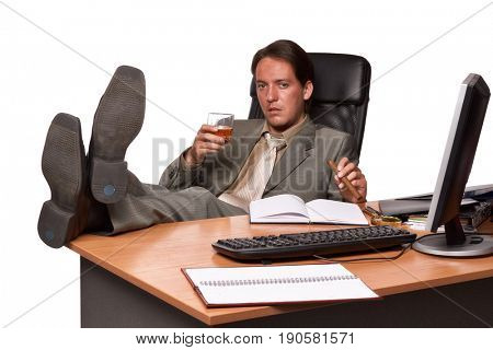 Businessman with cigar and glass of whisky  on workplace  on a white background.
