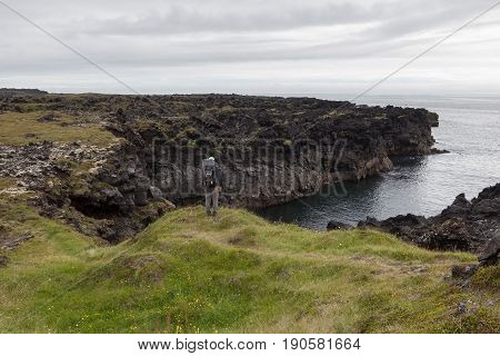 Snaefellsness, Iceland - July 23, 2016. Young Man With Big Backpack Standing On Green Thick Icelandi