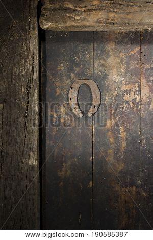 Rusty horseshoe on an ancient wooden door