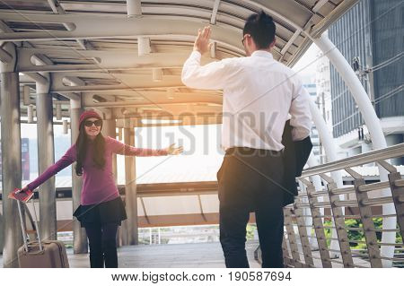 Couple travellers saying hello when meet each other at airport with traveling bag or luggage for travel abroad.